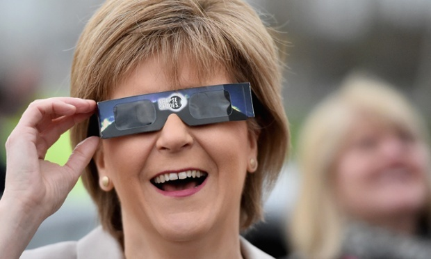 Nicola Sturgeon uses protective glasses to look into the sky at a partial solar eclipse in Glasgow, Scotland. Photograph: Jeff J Mitchell/Getty Images